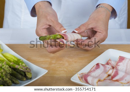 Chef wrapping asparagus with bacon slices in the kitchen of the restaurant - stock photo