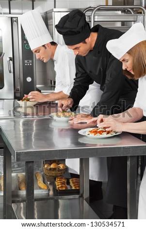 Chefs garnishing pasta dishes on restaurant kitchen counter - stock photo