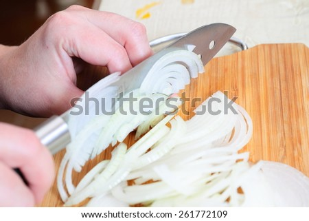 Chefs hands chopping onion on cutting board - stock photo
