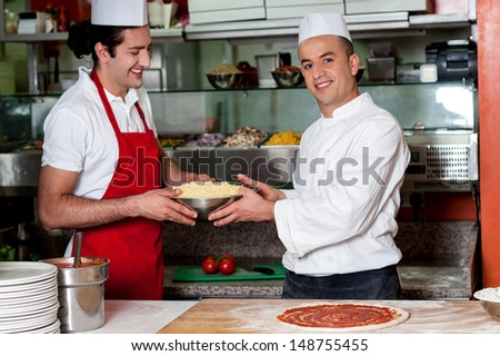 Chefs helping each other to make pizza - stock photo