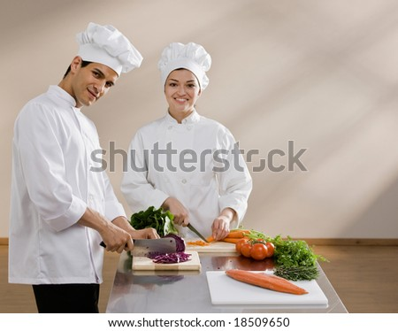 Chefs in toques and chef?s whites preparing and chopping fresh vegetables together - stock photo