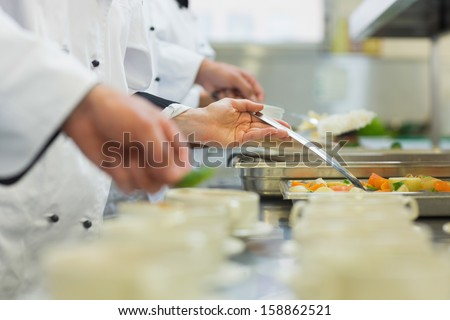 Chefs standing in a row preparing food in a modern kitchen - stock photo
