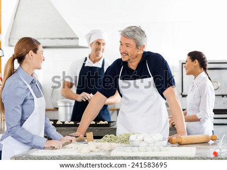 Chefs talking while preparing pasta with colleagues working in background at commercial kitchen - stock photo