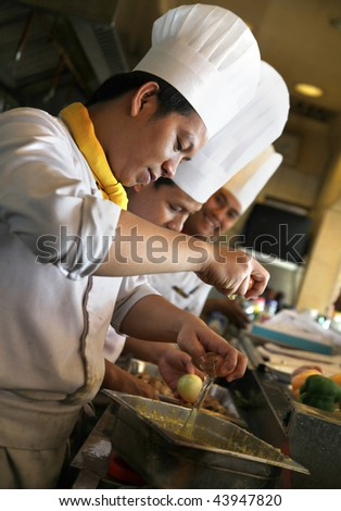 chefs working in the kitchen - stock photo