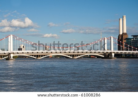 Chelsea Bridge over the river Thames against blue sky with white clouds and with Battersea Power station - stock photo