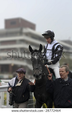 CHELTENHAM, GLOUCS, APRIL 17 2009: Jockey Richard Johnson rides Quentin Collonges from the parade ring in the second race of the April National Hunt Meeting at Cheltenham Racecourse, UK - stock photo