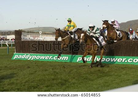 CHELTENHAM, GLOUCS; NOV 13: Jockeys battle over fences in the third race at Cheltenham Racecourse, UK, November 13, 2010 in Cheltenham, Gloucestershire - stock photo