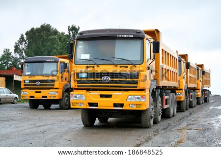 CHELYABINSK REGION, RUSSIA - AUGUST 8, 2008: New Hongyan CQ3304TTG306 dump trucks at the interurban road. - stock photo