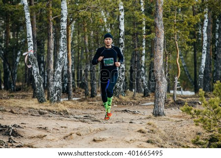 Chelyabinsk, Russia -  April 3, 2016: young male athlete running on track in spring forest during Spring half marathon
