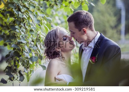 CHELYABINSK, RUSSIA - AUGUST 23, 2015 the couple the bride and groom  kissing on the street on a background of green foliage,  the light color in the style of instagram