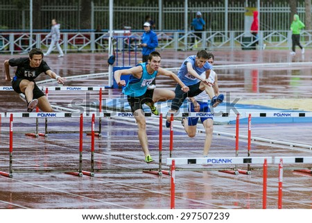 Chelyabinsk, Russia - July 10, 2015: group young athletes run 110 meter hurdles  in rain during Championship of Chelyabinsk on track and field athletics - stock photo