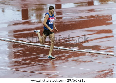Chelyabinsk, Russia - July 10, 2015: man athlet run sprint 400 meters in rain during Championship of Chelyabinsk on track and field athletics - stock photo