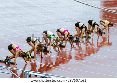 Chelyabinsk, Russia - July 10, 2015: young girl athletes ready for start of sprint distance of 100 meters during Championship of Chelyabinsk on track and field athletics - stock photo