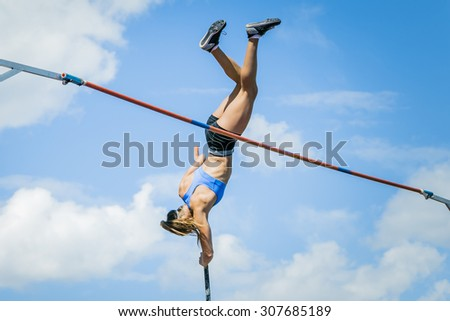 Chelyabinsk, Russia - July 24, 2015:  young woman athlete jumping with a pole overcomes bar during National competitions in memory of G. I. Nicewhen athletics - stock photo