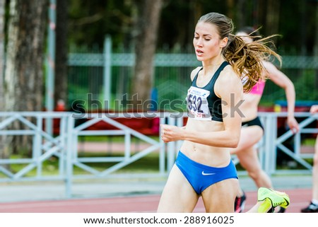 Chelyabinsk, Russia - June 10, 2015: young beautiful girl athlete running a sprint distance in stadium during Universities championship of Chelyabinsk region in athletics - stock photo