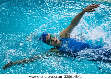 Chelyabinsk, Russia - October 21, 2015: girl athlete swims backstroke, around her spray of water during Championship of Chelyabinsk swimming