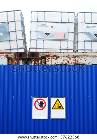 Chemical container, blue wall and warning signs - stock photo