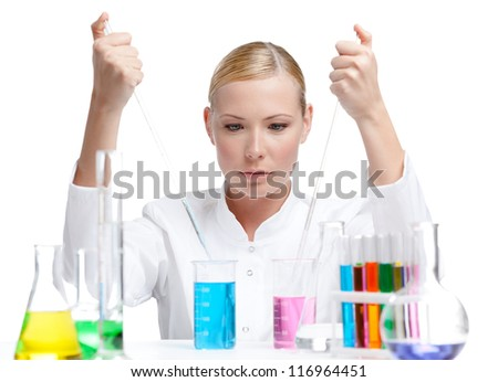 Chemical female researcher surrounded with vials and flasks makes some experiments, isolated on white - stock photo