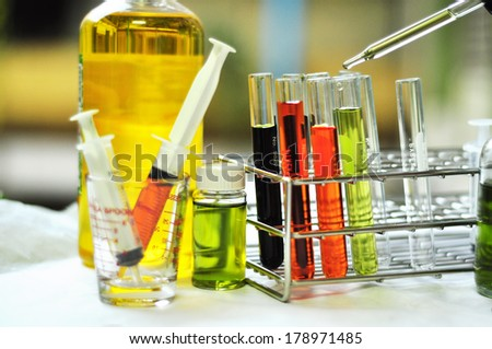 Chemical flask with a blue laboratory test tubes inside - stock photo