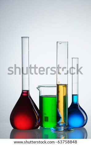 Chemical flasks with reagents over white - stock photo