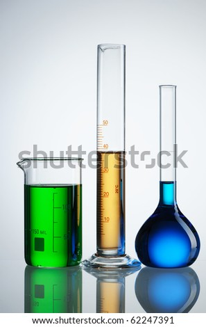 Chemical flasks with reagents over white - green, yellow and blue - stock photo