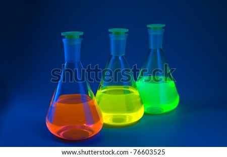 Chemical flasks with the liquids, shone different colors on a dark blue background. Shallow depth of field. - stock photo