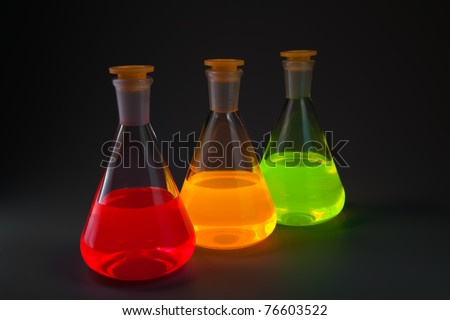 Chemical flasks with the liquids, shone different colors on a dark grey background. - stock photo