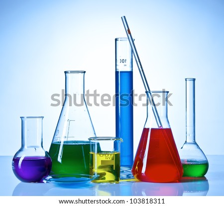 Chemical glassware with colored liquids inside bottles - stock photo