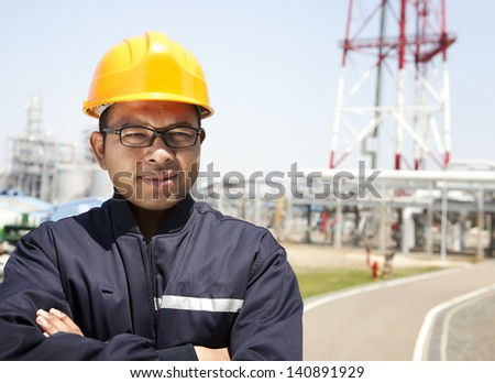 Chemical industrial engineer standing with oil refinery background - stock photo