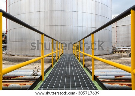 Chemical industry walkway with  fuel storage tank cladding Insulation. - stock photo