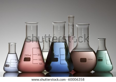chemical laboratory flasks containing liquid shiny color - stock photo