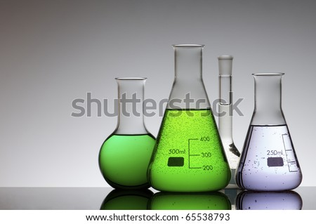 chemical laboratory flasks with colored liquid inside - stock photo