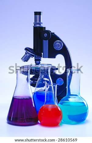 chemical laboratory glassware and microscope - stock photo