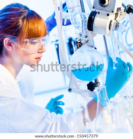 Chemical laboratory scene: attractive young PhD student scientist observing the blue indicator color shift after the solution  destillation. - stock photo