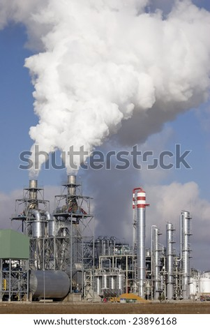 Chemical plant emitting white fumes in the atmosphere - stock photo