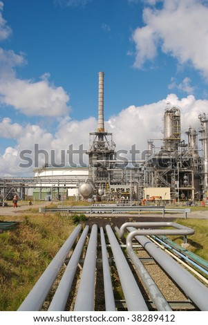 Chemical plant with a number of pipes leading towards it. - stock photo