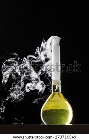 Chemical reaction in volumetric flask glass in labolatory - studio shoot - stock photo