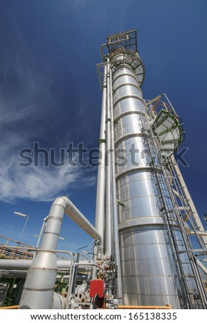 Chemical refinery tower in sunny day - stock photo