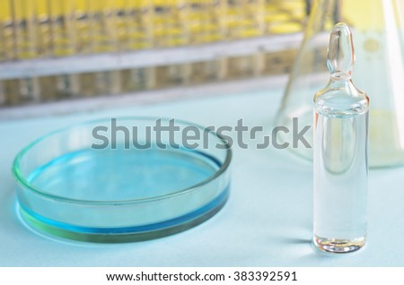 Chemical research in Petri dishes on blue background. Preparing plates in a microbiology laboratory. Inoculating plates. Vaccine ampoule. Natural light. - stock photo