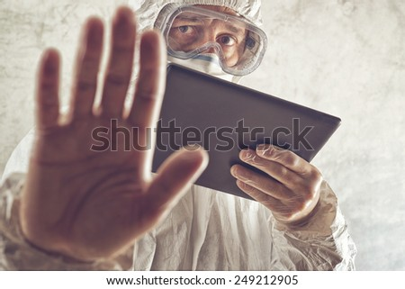 Chemical Scientist Holding Digital Tablet Computer and Gesturing Stop Sign. Chemical disaster, pollution or virus threat conceptual image with selective focus and shallow DOF. - stock photo