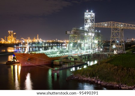 Chemical tanker moored at loading terminal at night