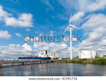 chemical tankers moored in amsterdam harbor next to a large windmill - stock photo
