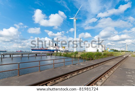 chemical tankers moored in amsterdam harbor next to a large windmill and railroad - stock photo