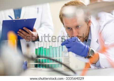 Chemical technician observing and checking liquid from test tube - stock photo