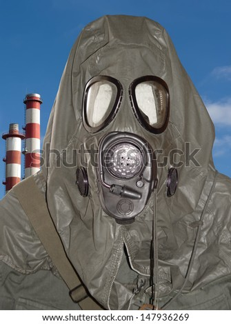 Chemical warfare suit against industrial background. - stock photo