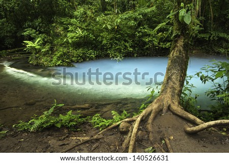 Chemicals contained within the waters of two rivers react to create a vivid blue color. - stock photo