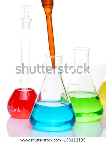 Chemicals in flasks and tubes on lab table - stock photo