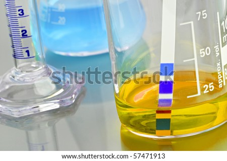 Chemicals in lab glassware with PH indicator - stock photo