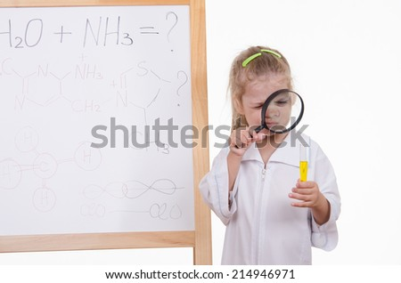 Chemist closely examines the liquid in a test tube - stock photo