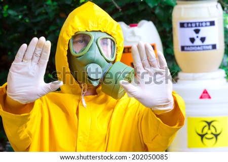 Chemist in protective clothing with gas mask gives a warning sign,photography - stock photo